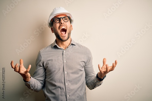 Young architect man wearing builder safety helmet over isolated background crazy and mad shouting and yelling with aggressive expression and arms raised Canvas Print