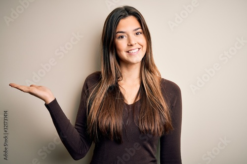 Young beautiful girl wearing casual sweater standing over isolated white background smiling cheerful presenting and pointing with palm of hand looking at the camera.