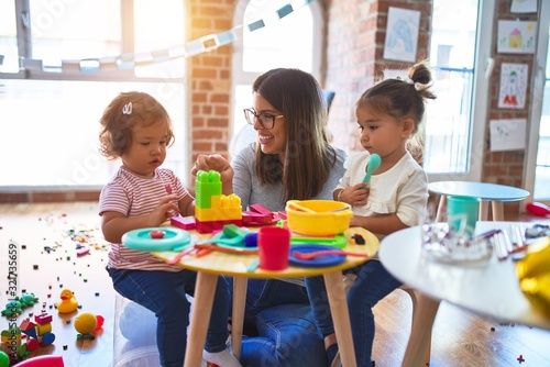 Obraz Young beautiful teacher and toddlers playing on the table with lots of toys at kindergarten - fototapety do salonu