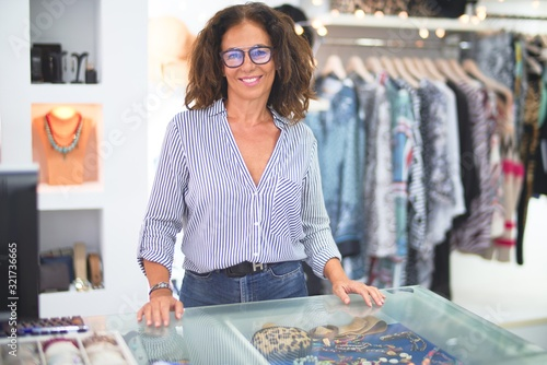 Cuadros en Lienzo Middle age beautiful clothes shop owner woman smiling happy and confident waitin