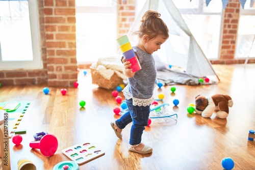 Obraz Beautiful toddler standing playing with colorful plastic cups at kindergarten - fototapety do salonu