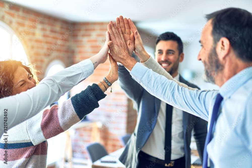 Fototapeta Group of business workers standing with hands together highing five at the office