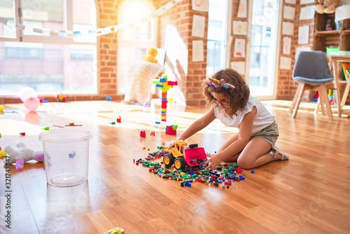Obraz Beautiful toddler wearing glasses and unicorn diadem playing with tractor and building blocks at kindergarten - fototapety do salonu