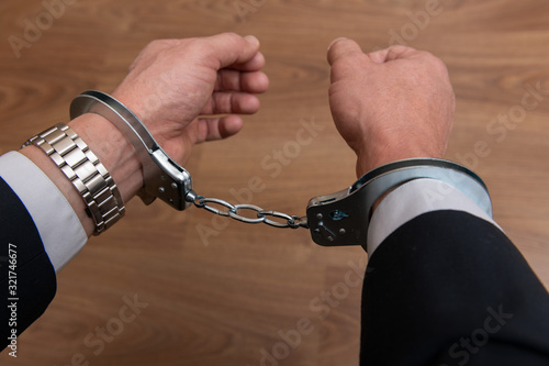 Arrested businessman or official in handcuffs Wallpaper Mural