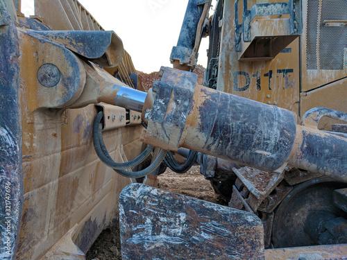 Photo Muddy Caterpillar D11 Bulldozer - Hydraulic Actuator Detail at Sunset