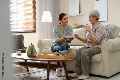 Obraz Young woman serving dinner for elderly woman in living room. Senior people care - fototapety do salonu