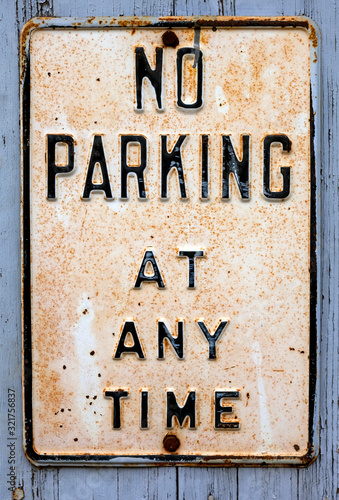Photo Weathered and rusty NO PARKING AT ANYTIME sign mounted on wall.