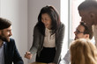 Middle aged Asian businesswoman talking to diverse colleagues at meeting