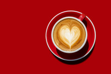 Top View Hot Cappuccino Coffee And With A Cream Like The Heart In A Red Cup Placed On Red Tone Ground. Isolated With Clipping Path. Love And Coffee Concept For Backdrop