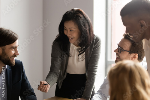 Obraz Middle aged Asian businesswoman talking to diverse colleagues at meeting - fototapety do salonu