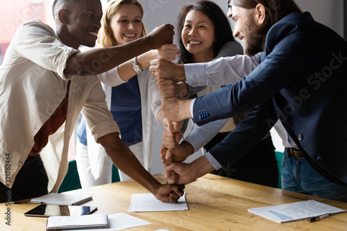 Fototapety, obrazy: Happy diverse employees stack fists at corporate meeting, celebrating success