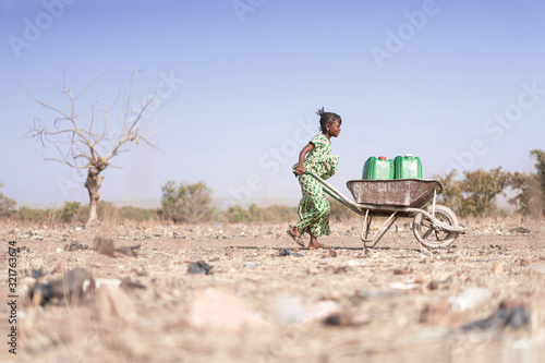 Photographie Little African Woman Transporting Fresh Water as a drought symbol
