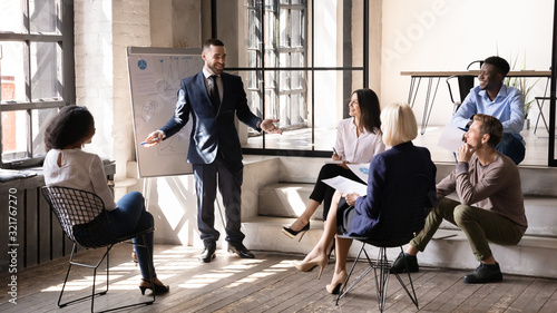 Positive ceo make presentation on flipchart for staff in office - 321767270