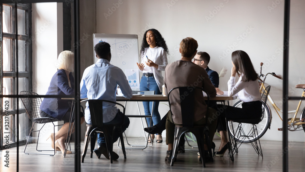 Fototapeta Diverse workers listening african businesswoman tell about strategy at meeting