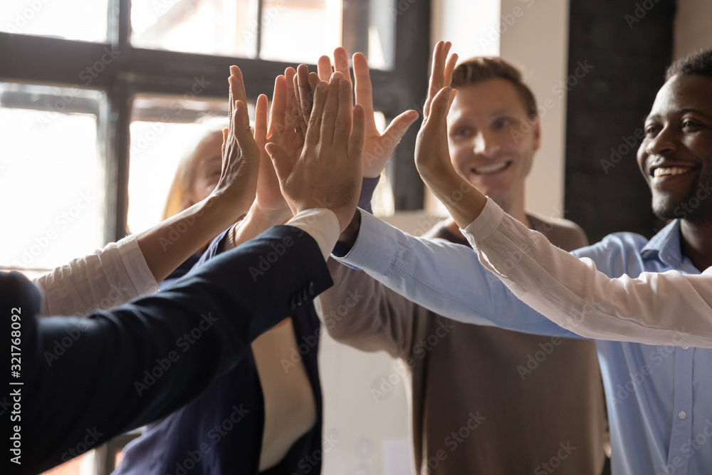 Fototapeta Closeup different ethnicity businesspeople raised hands giving high five