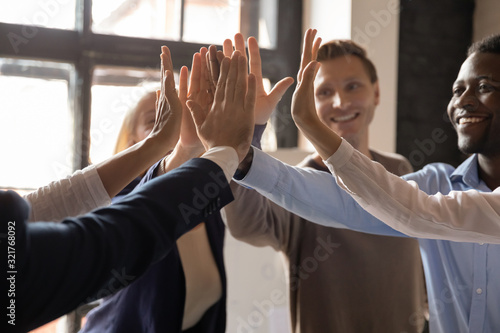 Fototapeta Closeup different ethnicity businesspeople raised hands giving high five obraz