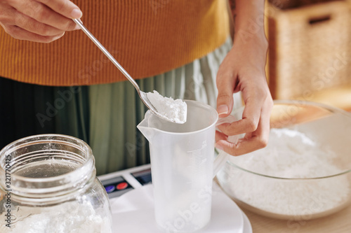 Fotografia, Obraz Close-up image of woman putting spoon of lye in plastic jar when making soap at