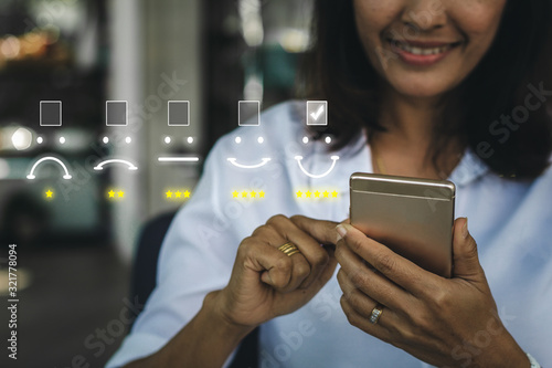 Cuadros en Lienzo Businesswoman pressing face emoticon on virtual touch screen at smartphone