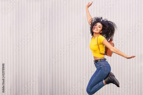Fotografie, Obraz Happy Arab woman jumping in urban background.