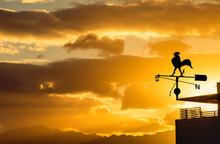 Silhouette Of Weather Vane With Decorative Metallic Rooster At Colorful Dawn. Concept Of Weather Forecasting