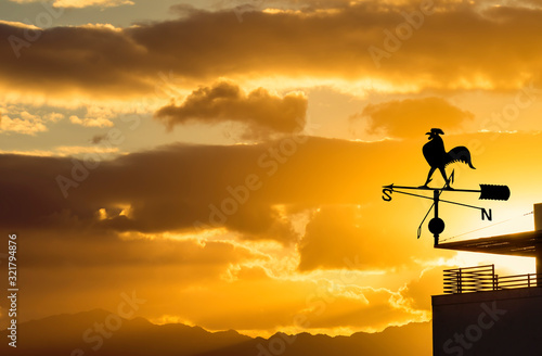 Fotografie, Tablou Silhouette of weather vane with decorative metallic rooster at colorful dawn