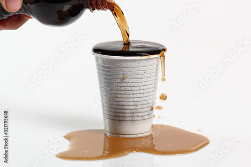 Fototapeta Human hand pouring cola from plastic bottle into overflowing disposable cup. Isolated on white background. obraz