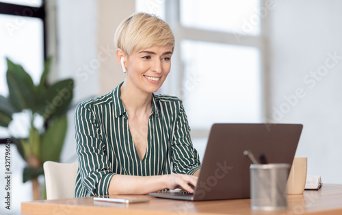 Mature Lady Working On Laptop In Earphones Sitting In Office Canvas Print