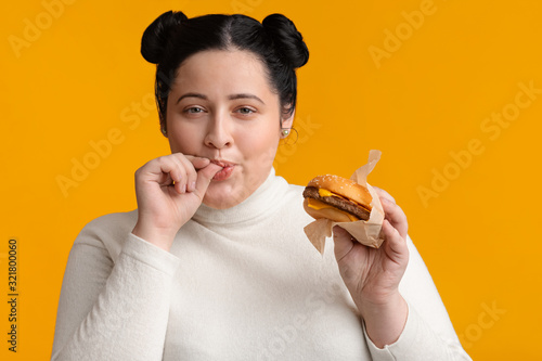 Young obese girl eating burger and licking fingers, enjoying fast food Canvas Print
