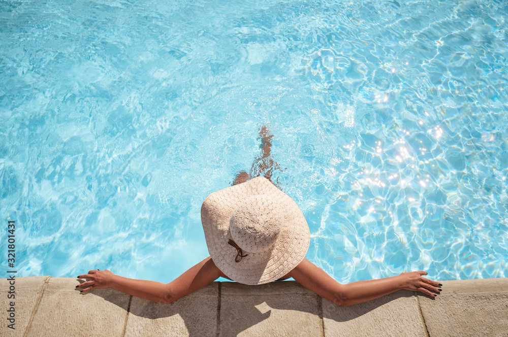 Fototapeta Young woman relaxing in the swimming pool with copy space
