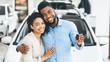 Leinwandbild Motiv Couple Showing New Car Key Smiling In Dealership Showroom, Panorama