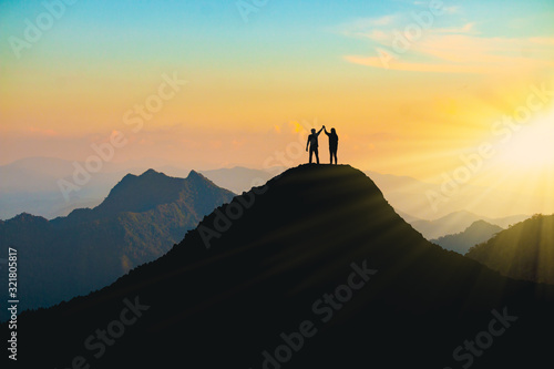 фотография The silhouette of lovers on the top of the mountain During sunset time