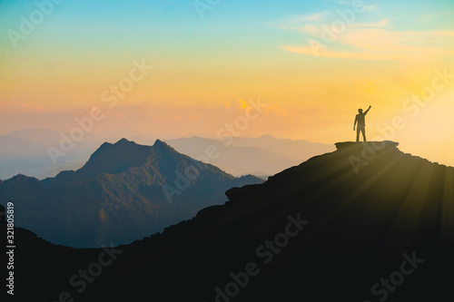 The silhouette of a man with a cheerful raise in his hand on the top of the moun Canvas Print