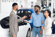 Couple Buying Car Taking Key From Salesman In Auto Showroom