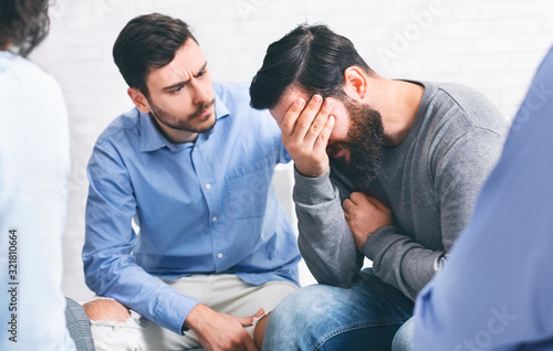 Group members comforting crying addicted man at rehab session Canvas Print
