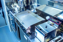 Equipment In The Cafe. Frying Surface In The Restaurant Kitchen. Stainless Steel Kitchen Equipment. Small Deep Fryer In The Kitchen Of The Dining Room. Hot Food Processing Line. Electric Frying Pan