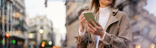 Obraz Young woman with smartphone on night street - fototapety do salonu