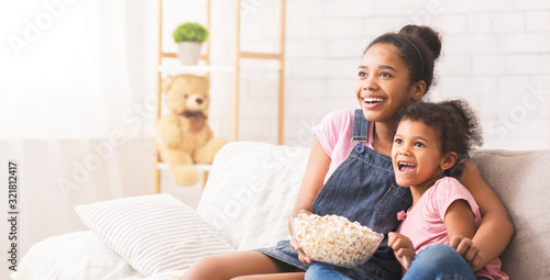 Fotografia, Obraz Two emotional african sisters watching tv and eating popcorn