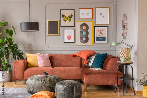 Fototapeta Vintage black poufs in trendy eclectic living room interior with brown couch obraz