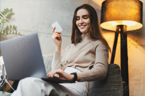 Pretty girl buying clothes online in international retail store, ordering shipping to her country Canvas Print