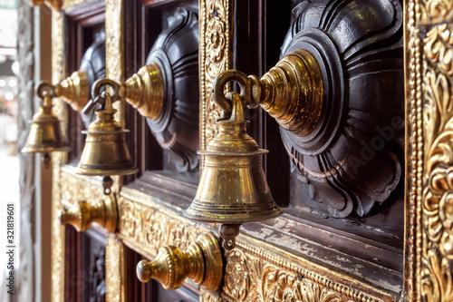 Fotografie, Obraz Antique bronze bells on a wooden door with inlaid Hindu temple