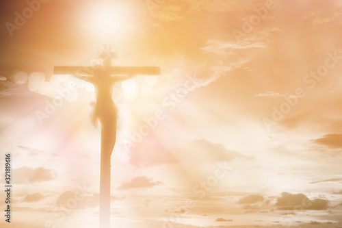 Slika na platnu silhouette Jesus Christ crucifixion on cross over orange sunset light background