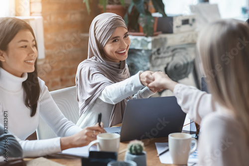 Two girls business colleagues shaking hands in office Canvas Print