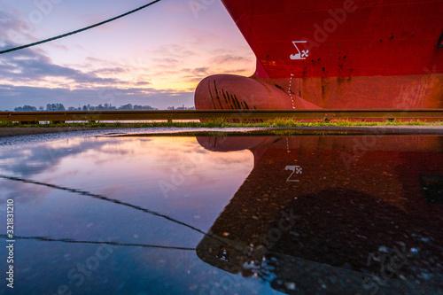 Fotomural Schiffsbug mit Spiegelung zum Sonnenuntergang