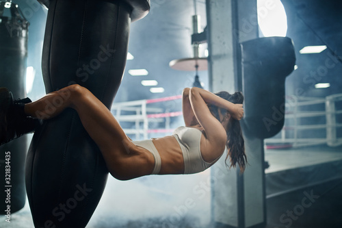 Woman training abs on punching bag.