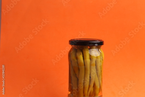 Photo chili peppers in glass canned jar with vinegar