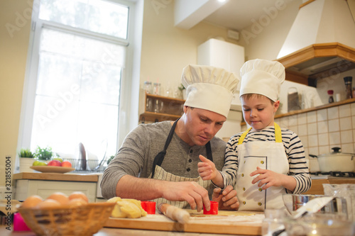 Photo Dad and son in chef's hats are cooking
