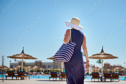 Fototapeta Woman in hat and blue dress go for a walk in the hotel resort near swimming pool with beach bag obraz