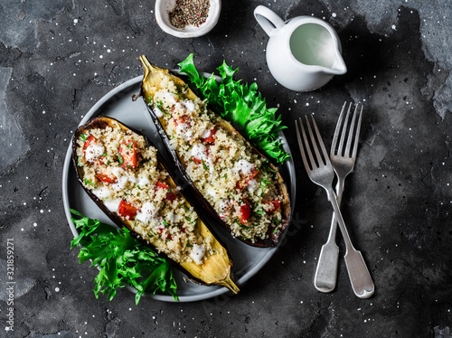 Fototapeta Grilled eggplant stuffed with couscous, tomatoes, cilantro with yogurt sauce on a dark background, top view obraz