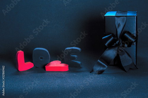 Black gift box and red word LOVE on dark background, copy space. Valentine's day, birthday romantic concept, greeting card.