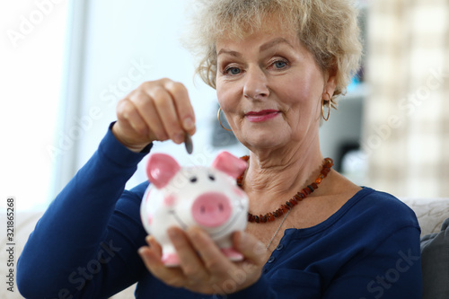 Fototapeta Elderly woman happily saves money in piggy bank. Older generation is used to saving and saving money. Closeup, an elderly woman is happy with her savings and puts coin in piggy bank. obraz